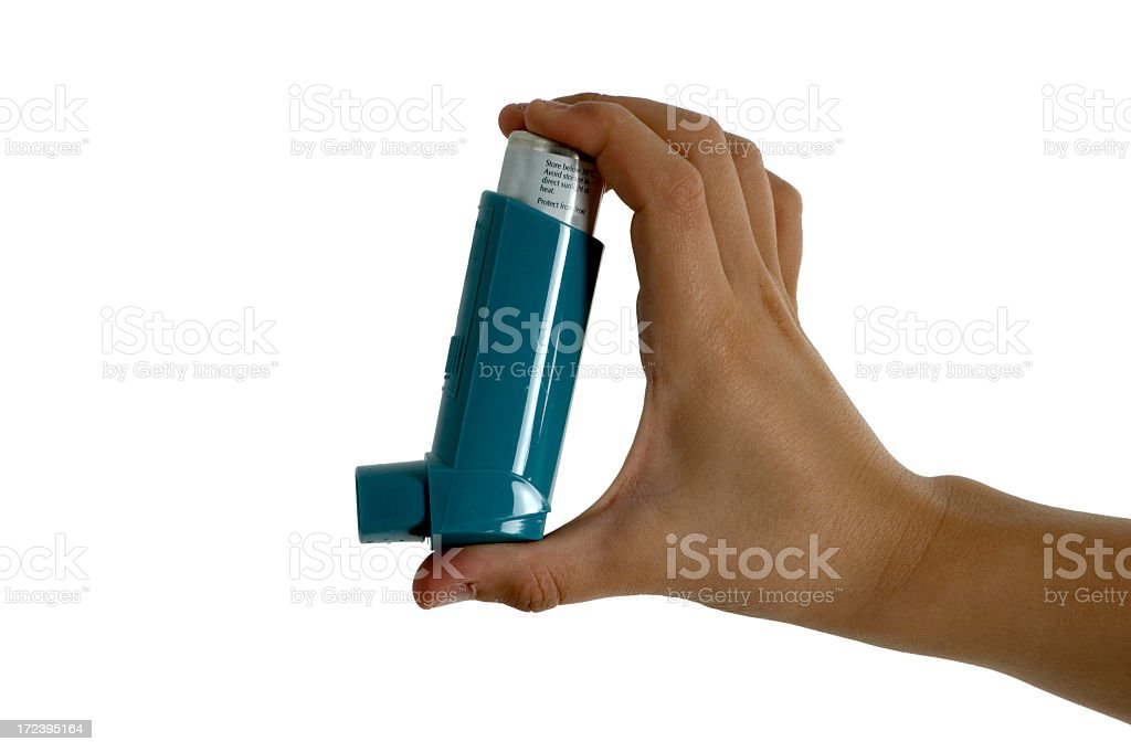 Hand holding an asthma inhaler against white background stock photo