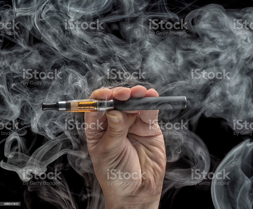 Hand holding an electronic cigarette over a dark background stock photo