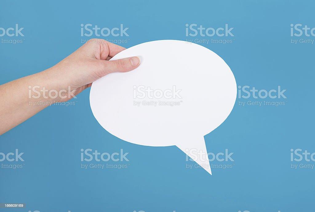 Hand holding an empty speech bubble stock photo