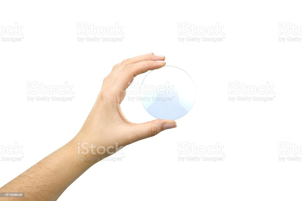 Hand holding an eyeglass lens without the glasses on white royalty-free stock photo