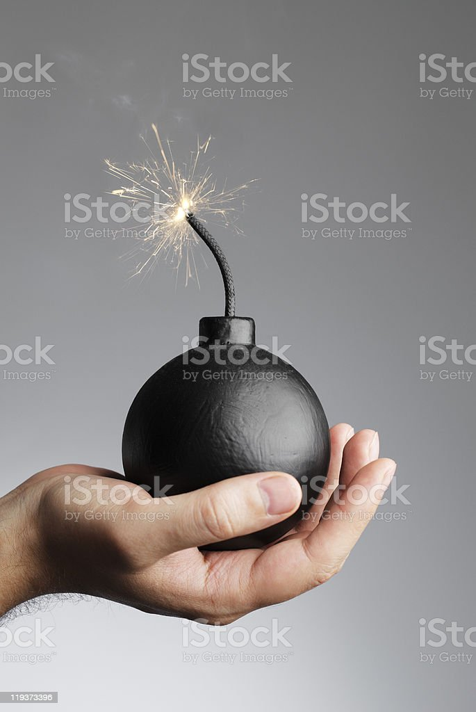 Hand holding an old style bomb that is lit about to explode stock photo