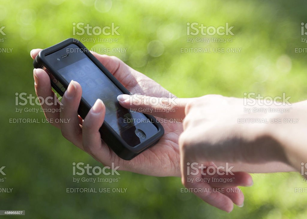 Hand holding and touching iPhone 4S royalty-free stock photo