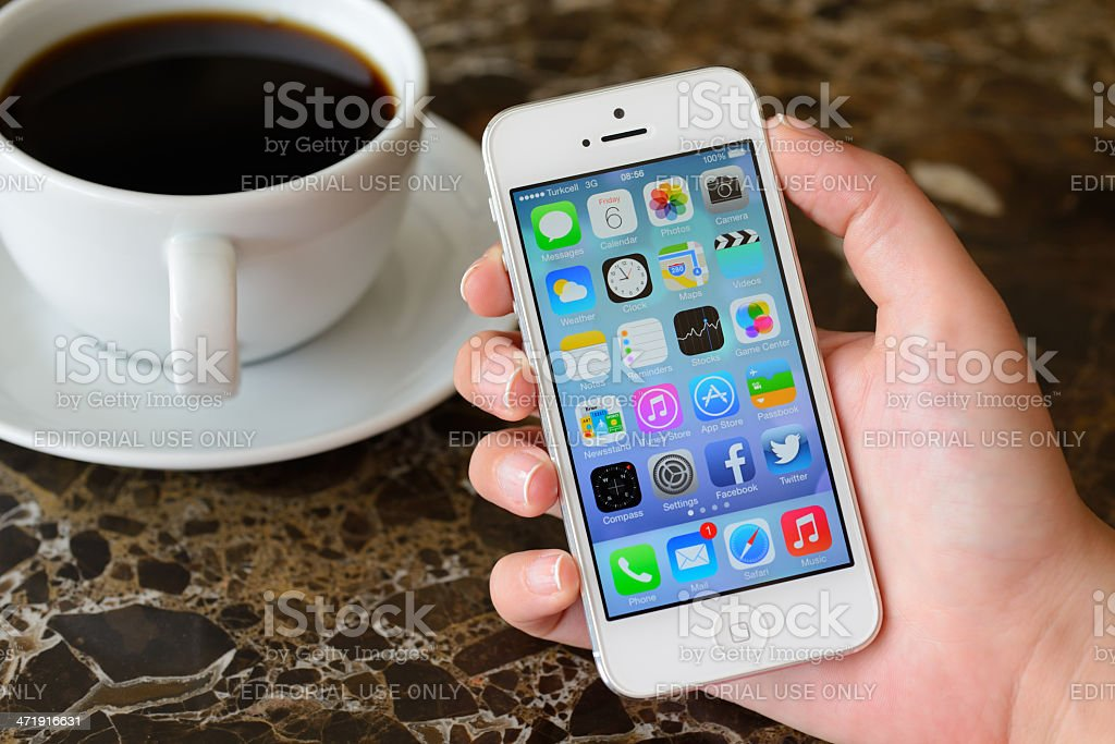 Hand holding Apple iPhone 5 displaying home screen stock photo
