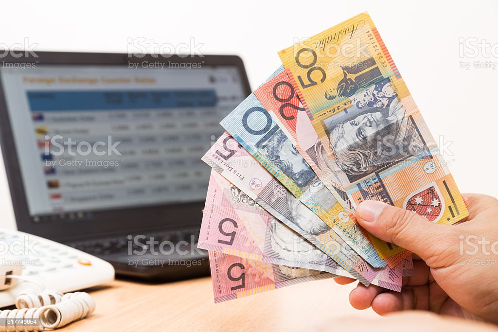 Hand holding Australian dollar in office with computer in background stock photo