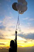 Hand holding balloons on the background of sunset sky