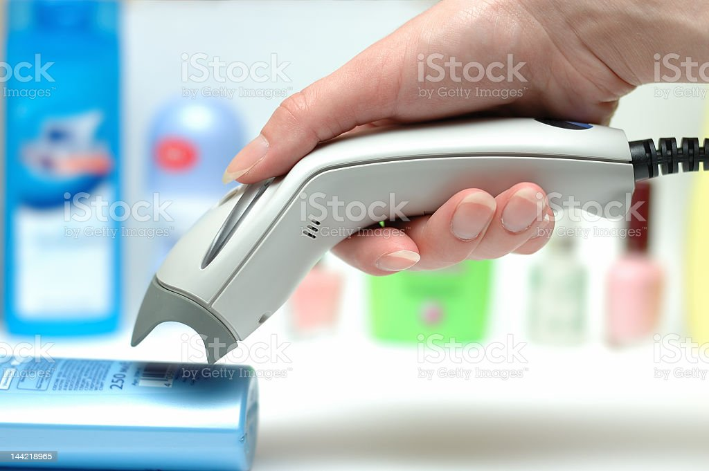 Hand holding barcode scanner to product barcode stock photo