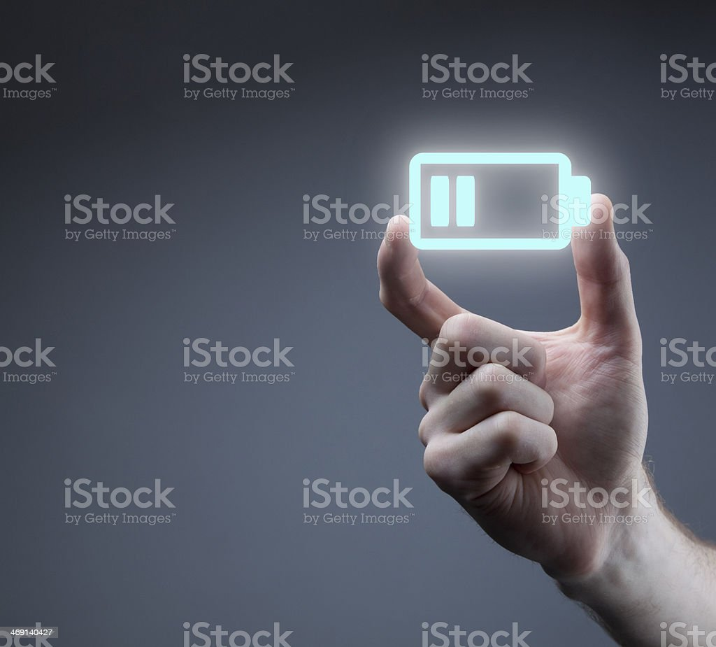 Hand holding battery icon stock photo