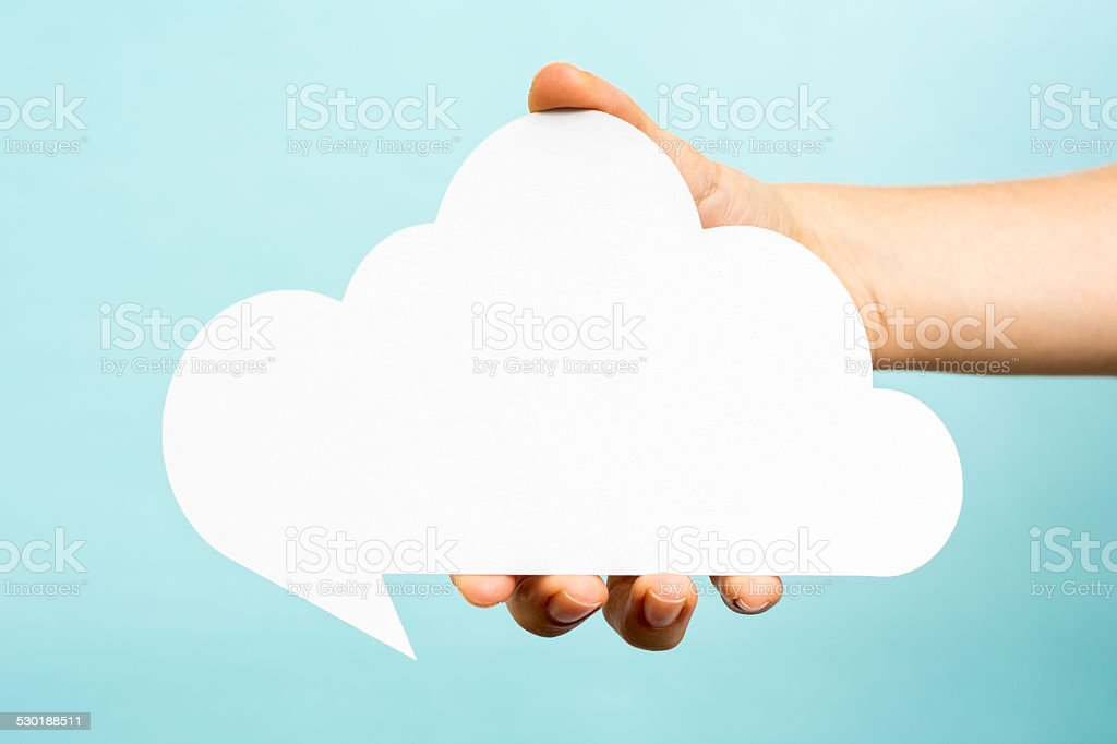 Hand holding big white empty speech bubble. Cloud computing concept stock photo