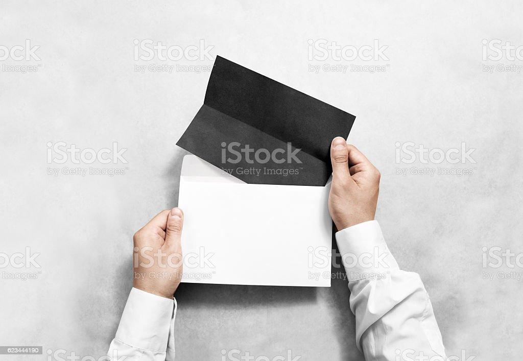 Hand holding black blank envelope and folded leaflet mockup stock photo