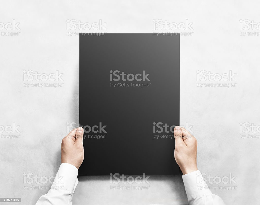 Hand holding black blank poster mockup, isolated. stock photo