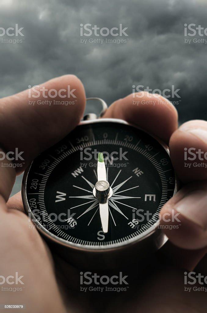 Hand holding black compass stock photo