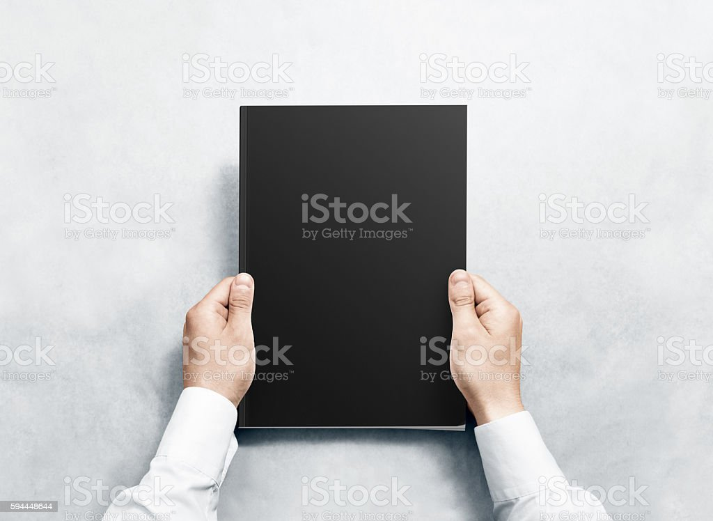 Hand holding black magazine with blank cover mockup. stock photo