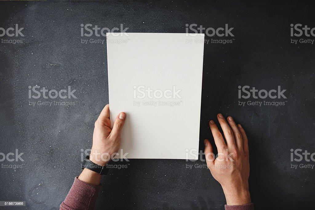 Hand holding blank brochure on black table stock photo
