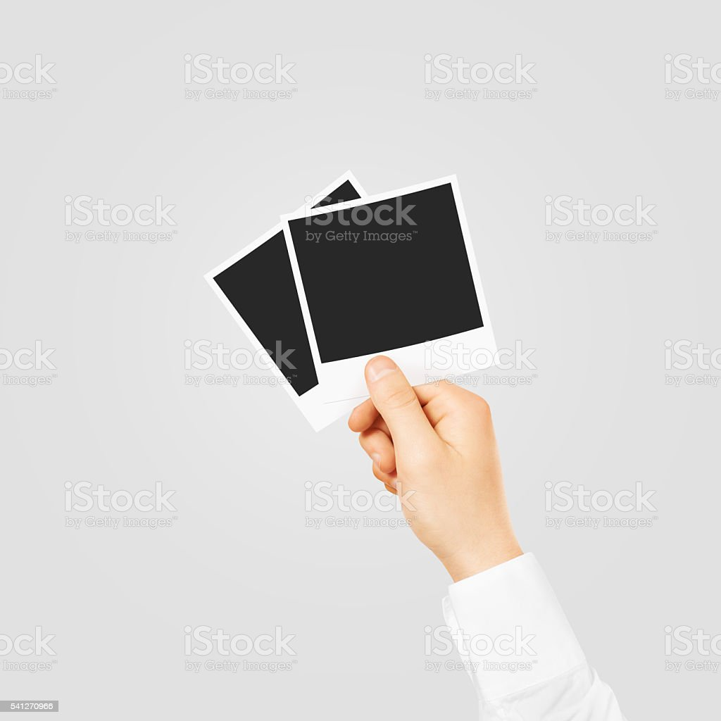 Hand holding blank photo frames mockup. Empty old photography te stock photo