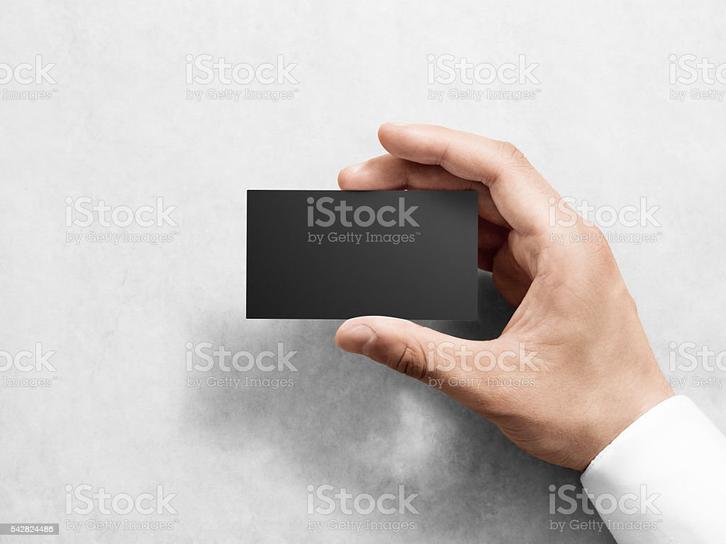 Hand holding blank plain black business card design mockup. stock photo