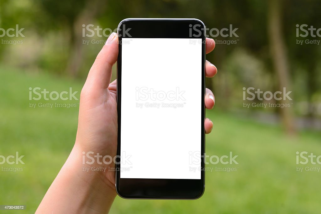 Hand holding blank screen smart phone in park stock photo