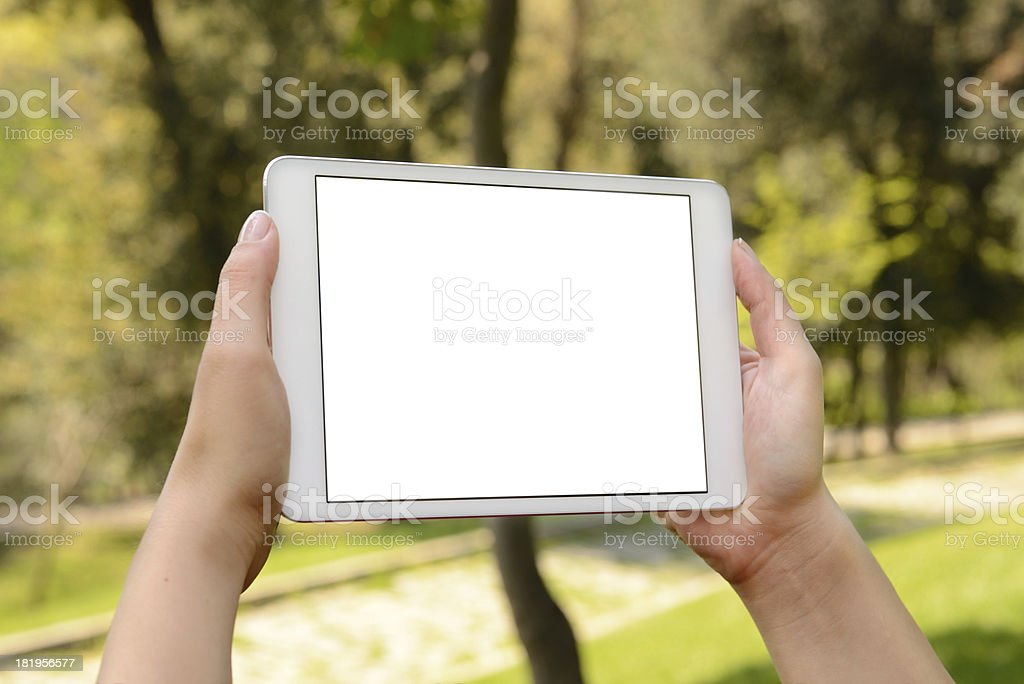 Hand holding blank screen tablet pc in park royalty-free stock photo