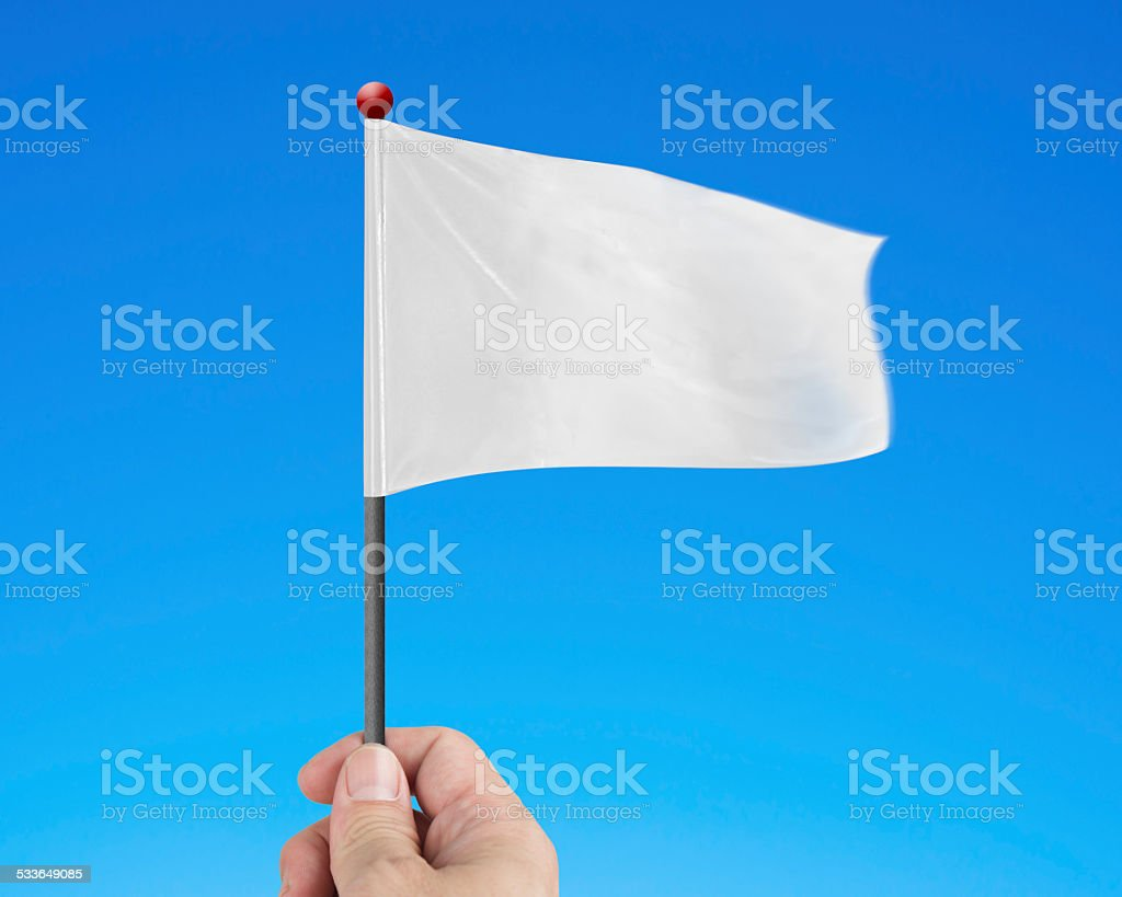 Hand holding blank white flag isolated on blue stock photo