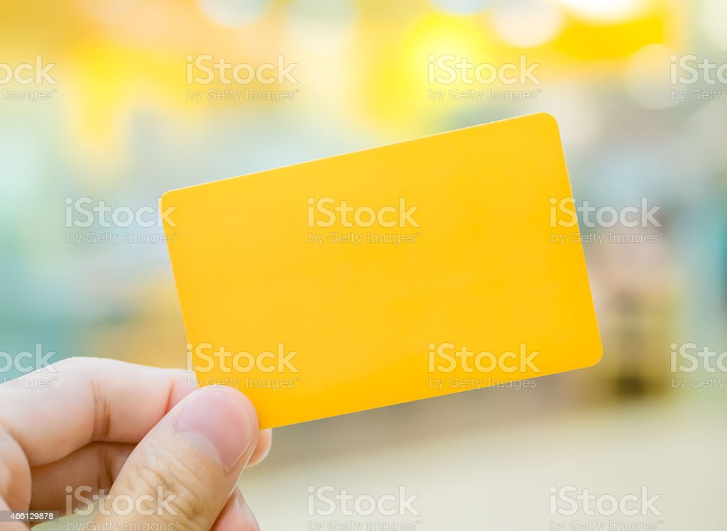 Hand holding blank yellow card stock photo