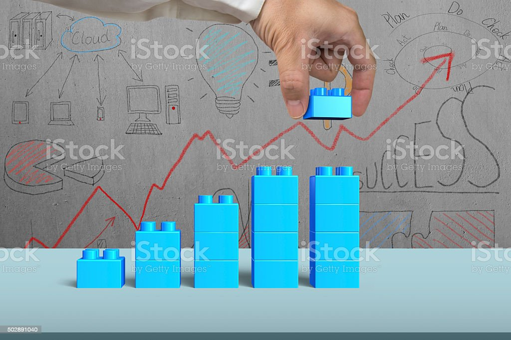 Hand holding blue block complete growth bar graph shape stock photo