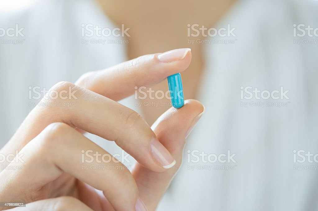 Hand holding blue capsule pill stock photo