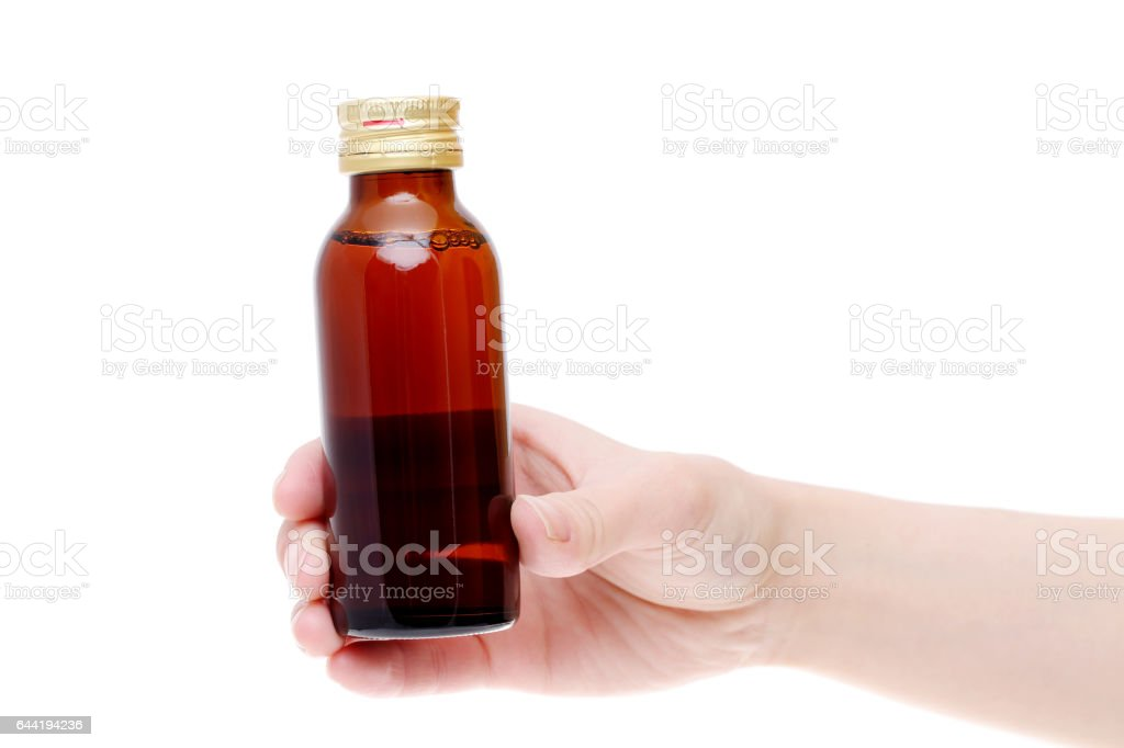 Hand holding brown medicine bottle stock photo