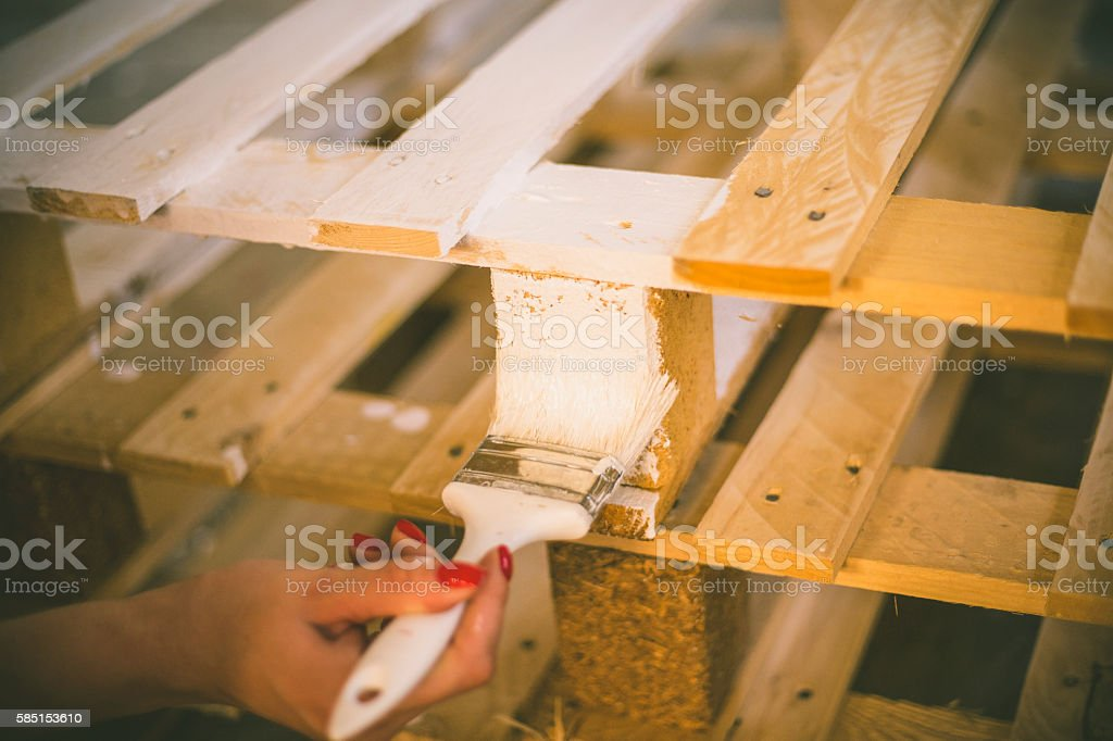 hand holding brush and paint timber stock photo