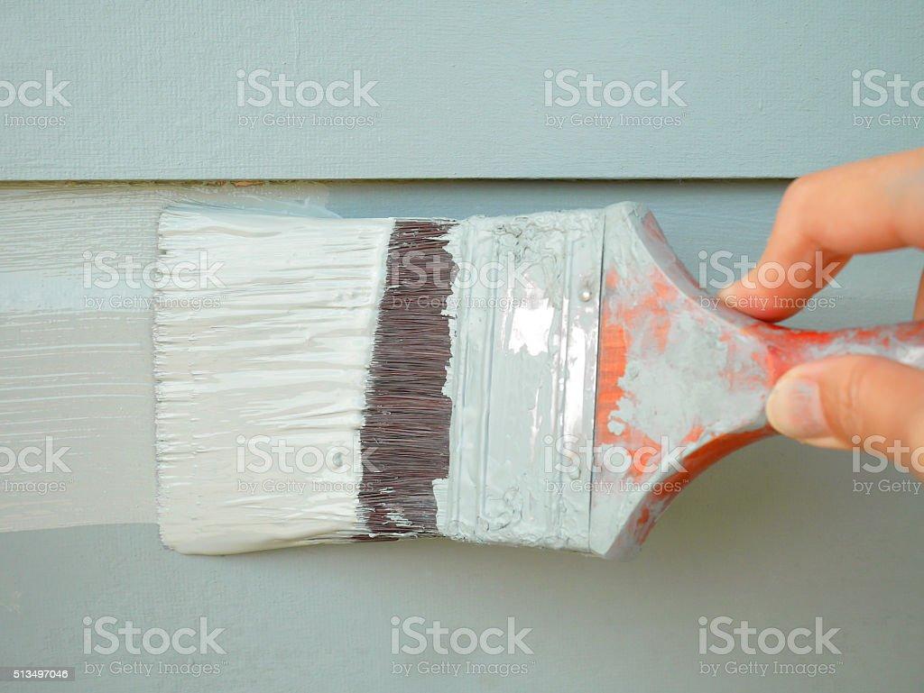Hand holding brush painting wall stock photo