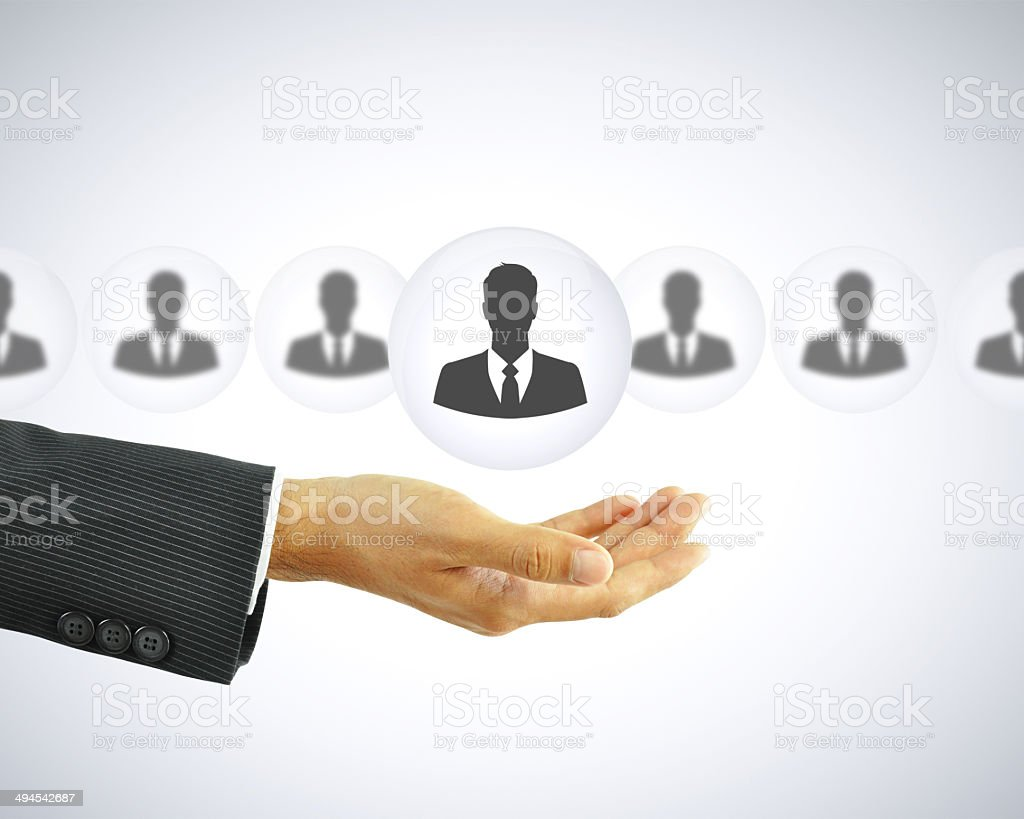 Hand holding businessman icon - HR concept stock photo