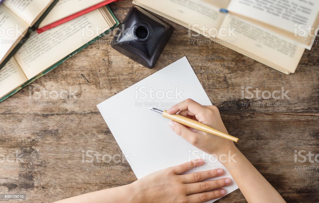 Hand holding calligraphy dip pen above white paper on wooden table with books stock photo