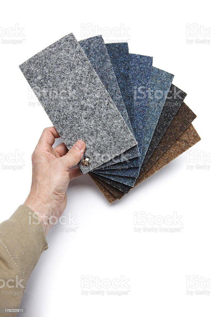 Hand holding carpet samples on white background royalty-free stock photo
