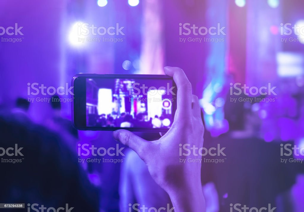 Hand holding Cell phone Camera Photo Shot on Concert event Crowd...