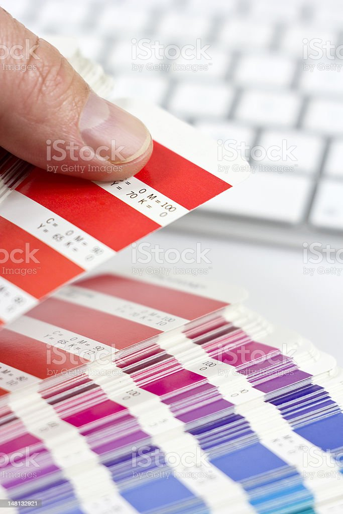 Hand holding colorful paint chips next to white keyboard royalty-free stock photo