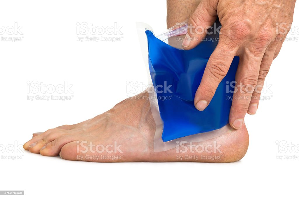 Hand Holding Cool Gel Pack On Ankle stock photo