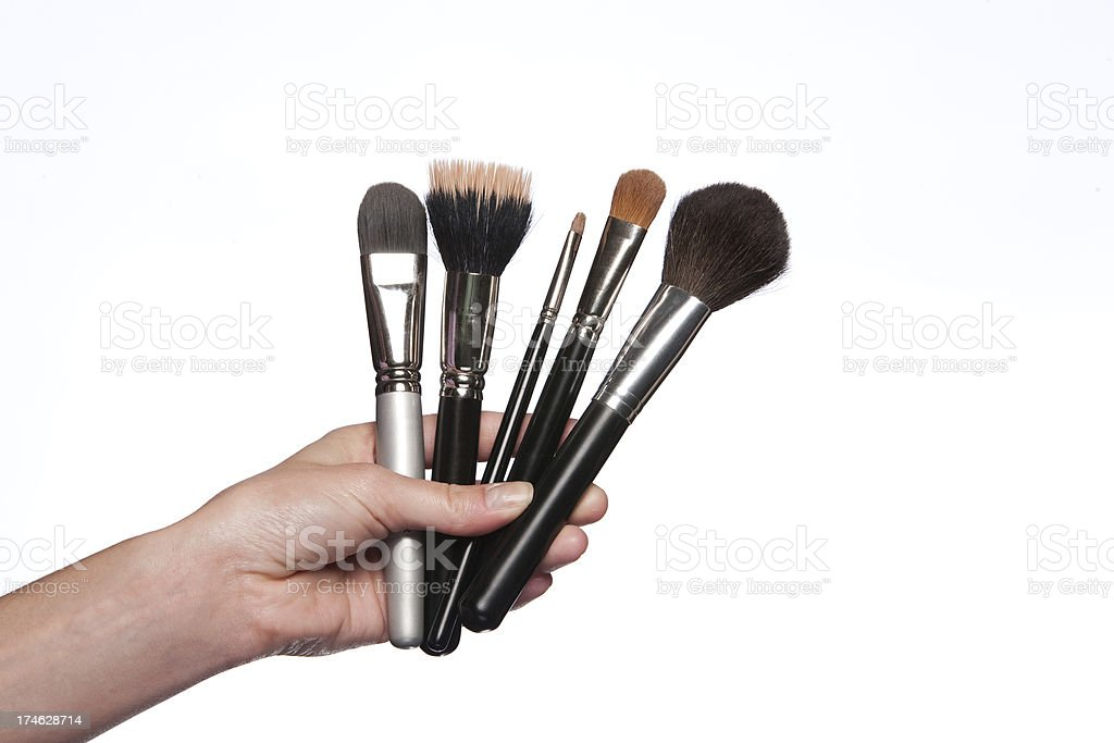 hand holding cosmetic brushes stock photo