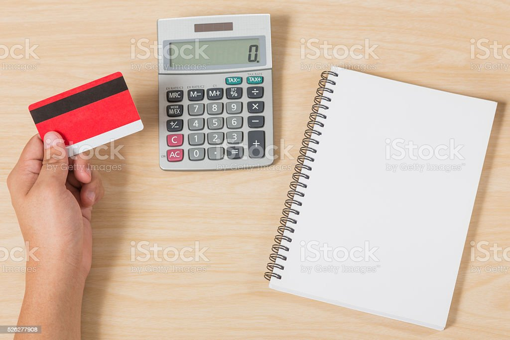 hand holding credit card and put calculator, notebook on wood stock photo