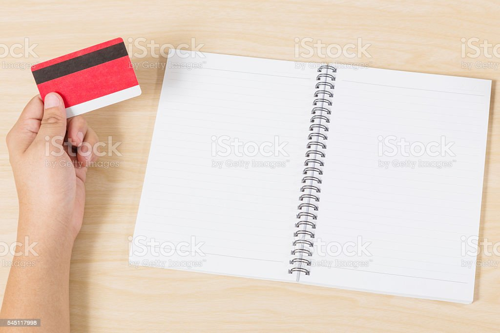 hand holding credit card and put notebook on wood stock photo