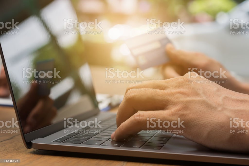 Hand holding credit card for online shopping on laptop ecommerce concept stock photo