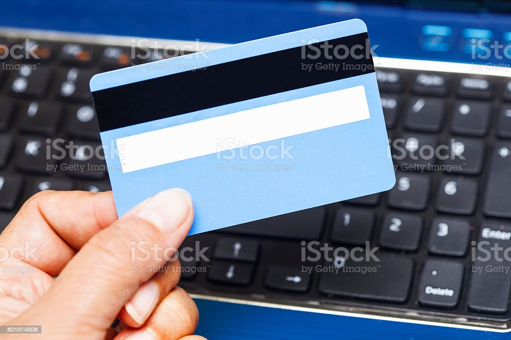 hand holding credit card on laptop stock photo
