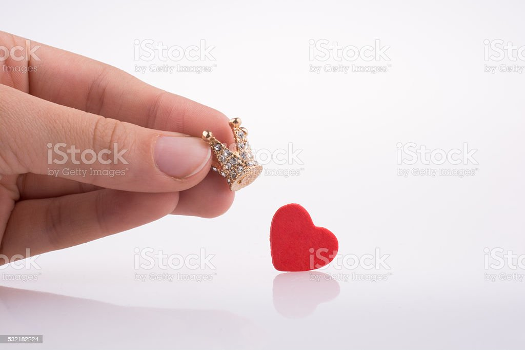 Hand holding crown near a heart stock photo