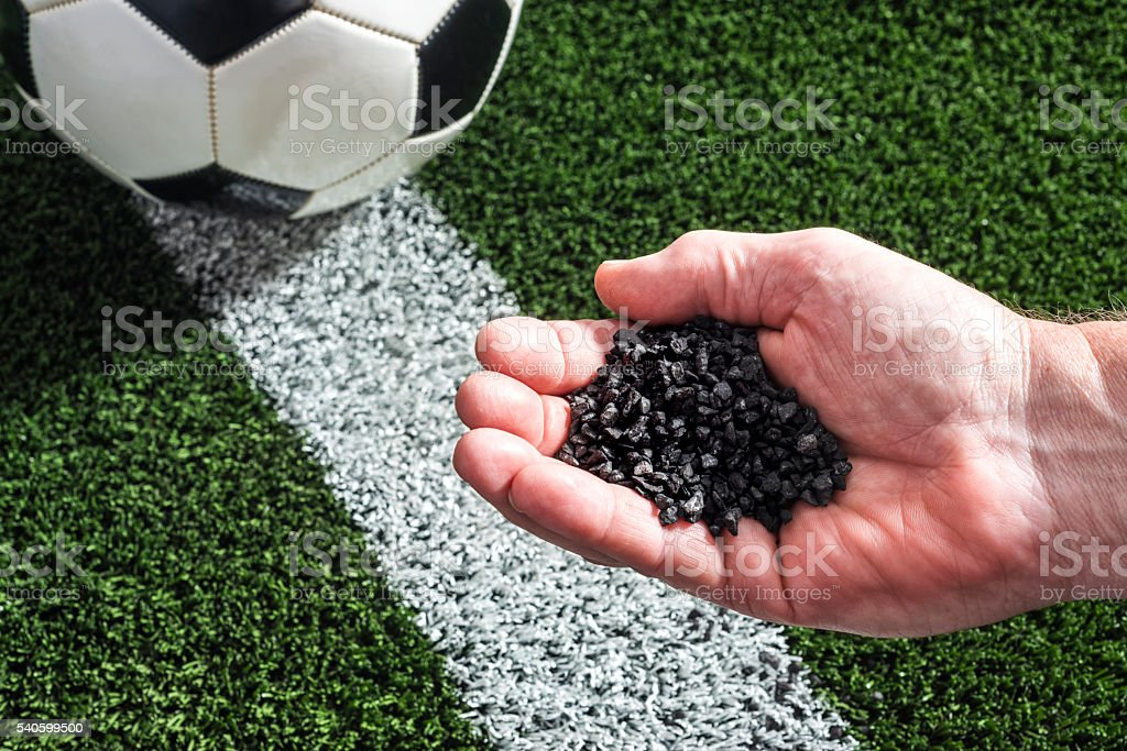 Hand holding crumb rubber over an artificial turf sports field stock photo