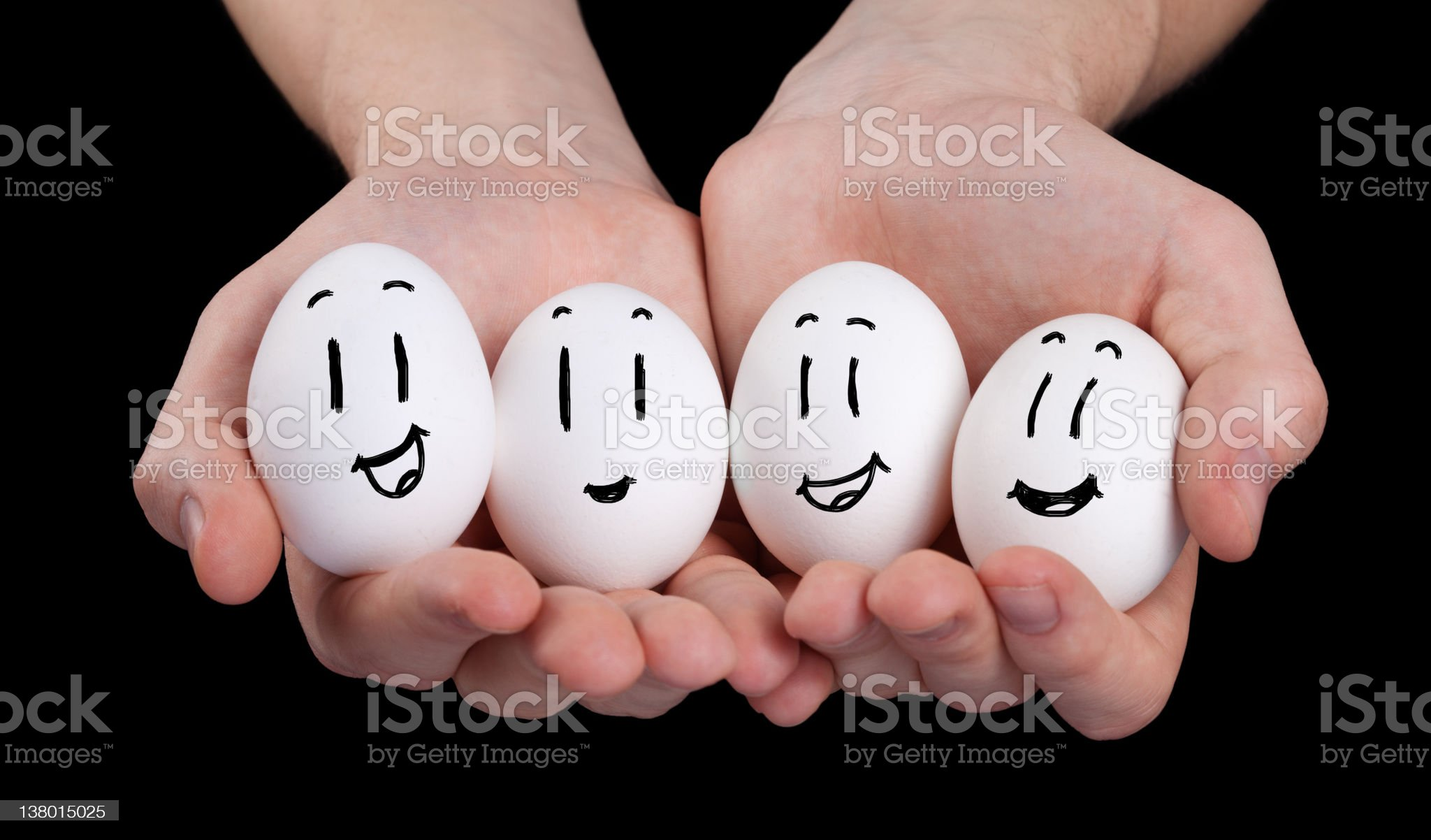 Hand holding cute eggs with funny face smileys royalty-free stock photo