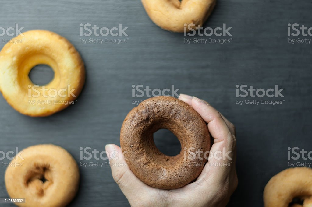 hand holding donut over donuts. stock photo