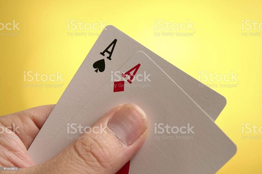 Hand Holding Double Aces on yellow stock photo