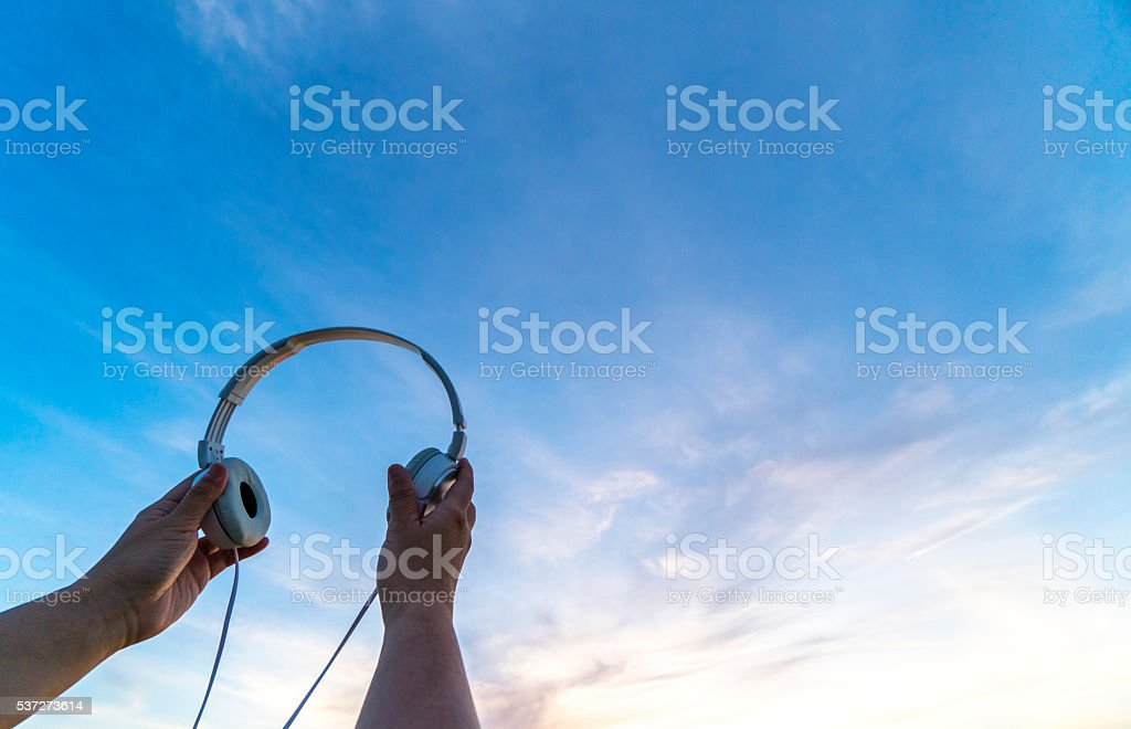 hand holding earphone, high in sky stock photo