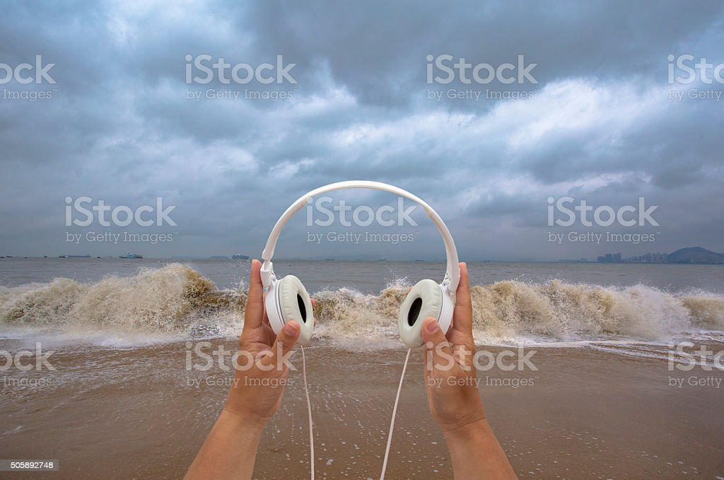 hand holding earphone on beach,listening to waves stock photo