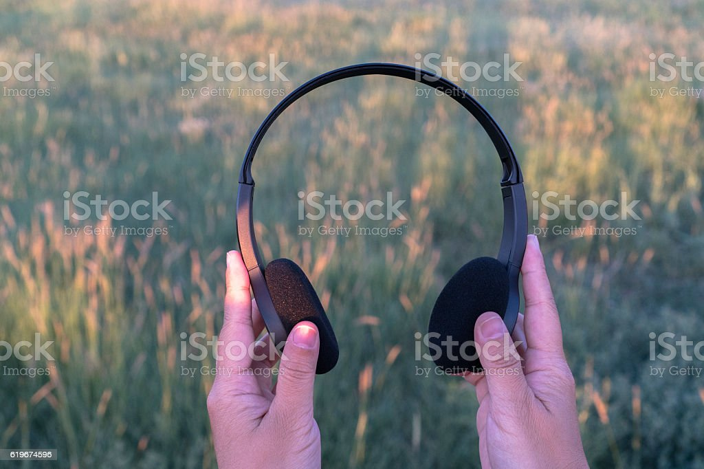 Hand holding earphone on pasture at sunset stock photo