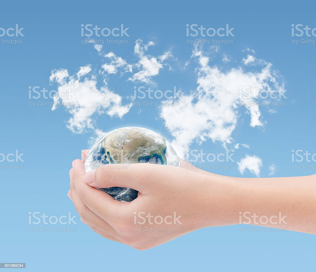 Hand holding earth on world clouds map background stock photo