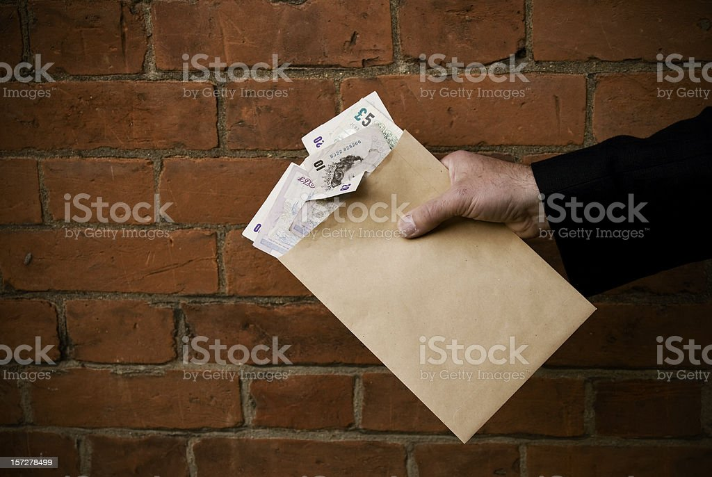 Hand holding envelope and bank notes stock photo