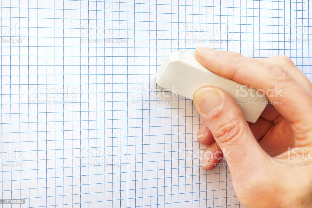 Hand holding eraser on graph paper royalty-free stock photo